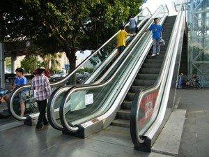"""乘坐自动扶梯:""""左行右立""""还是""""站稳扶好""""?"""