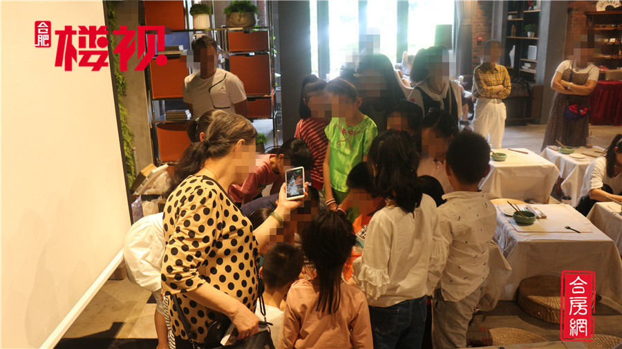 孩子们围绕老师学习制扇